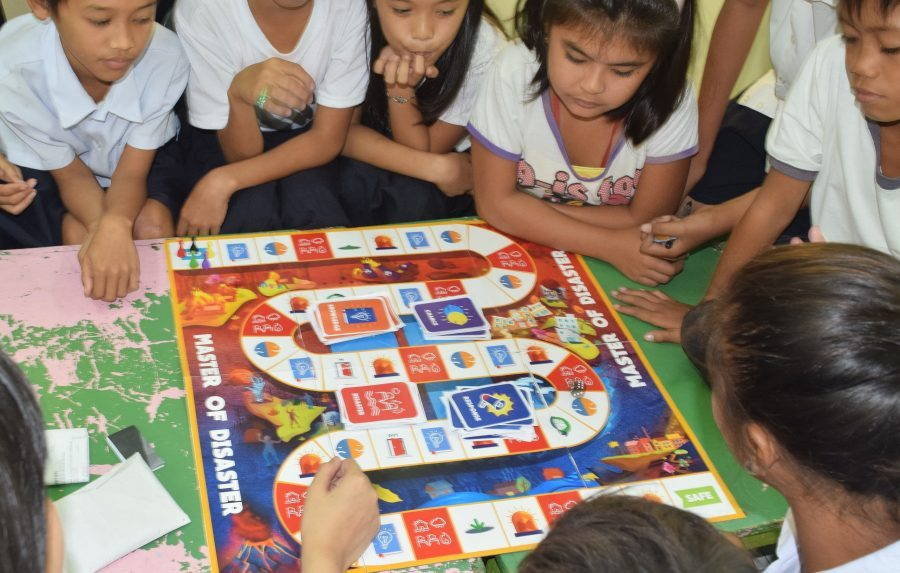 Children playing Master of Disaster boardgame